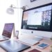 silver iMac near iPhone on brown wooden table