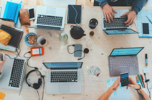 people sitting down near table with assorted laptop computers